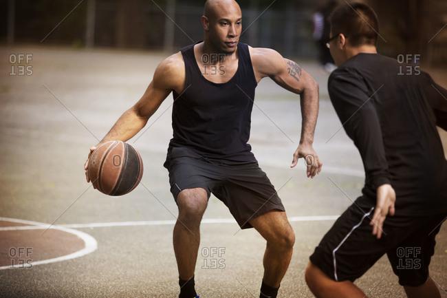 Three quarter length of man dribbling on basketball court
