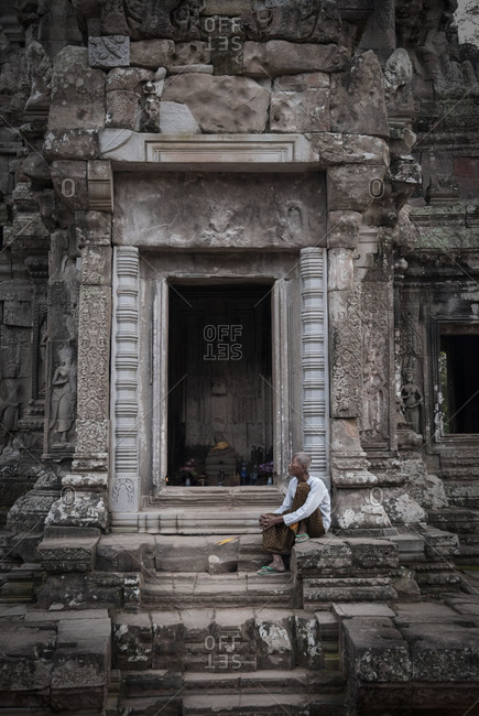 Angkor Wat, Cambodia - October 24, 2009: Woman sitting on the steps of a temple