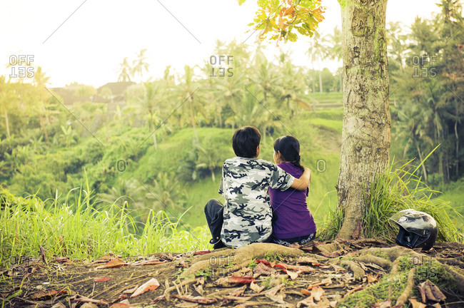 Couple sitting under a tree in Ubud, Bali