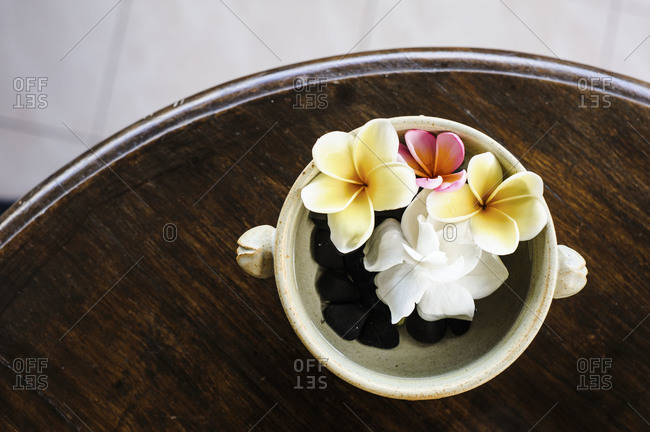 Fresh flowers arranged in a water bowl in a guesthouse in Ubud, Bali, Indonesia