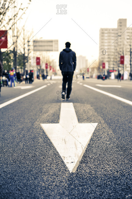 Man walking on a road with an arrow painted behind him
