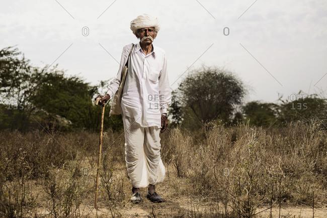 Jodhpur, India - January 31, 2013: Full length of Indian elderly man with cane