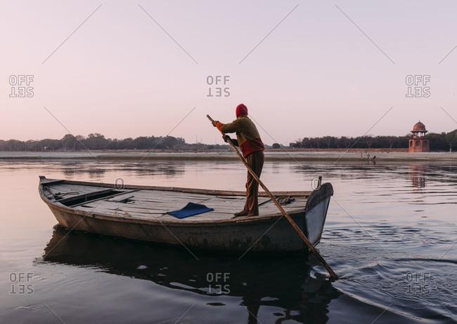 Man paddling on River Yamuna, India