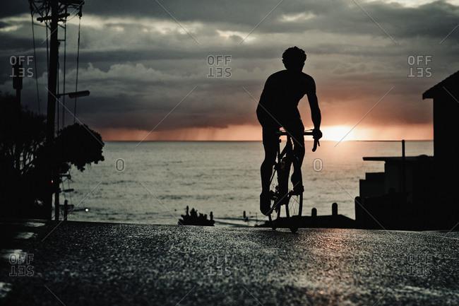 Man biking in a road nearby the ocean in Sydney, Australia