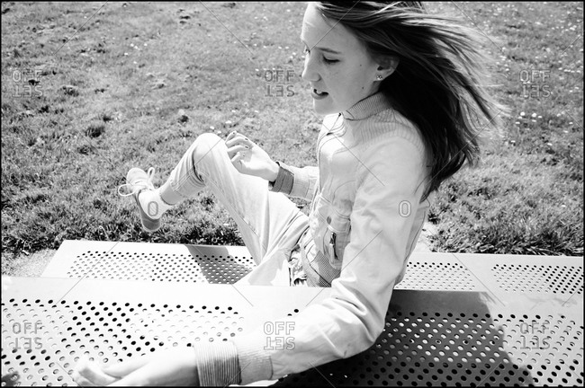 Teenager sitting on a bench in a park
