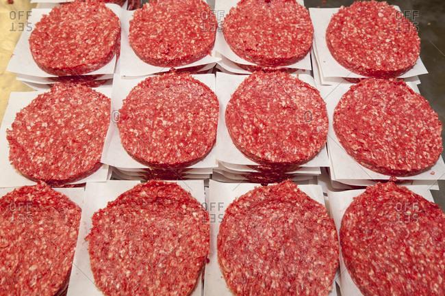 Hamburger patties stacked in rows