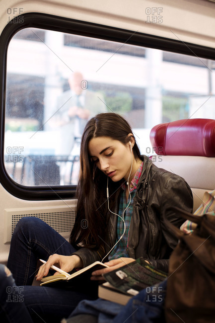 Young woman traveling by train and listening music