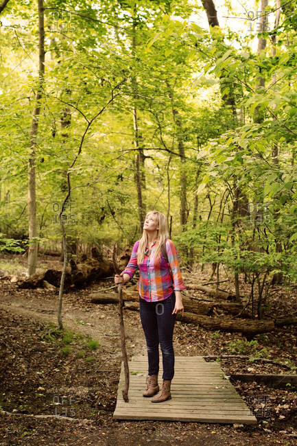 Blonde girl standing with stick on timber planks in the forest