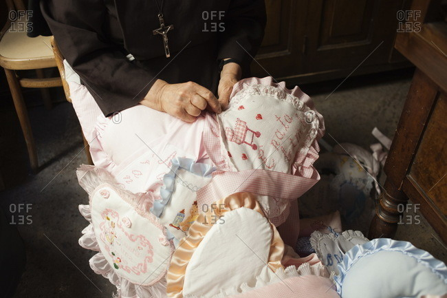 Nun sewing a ribbon for a baby in the Sanctuary of Santa Maria Francesca in Naples, Italy