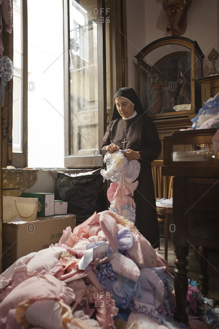 Naples, Italy - September 24, 2013: Nun sewing a ribbon in the Sanctuary of Santa Maria Francesca