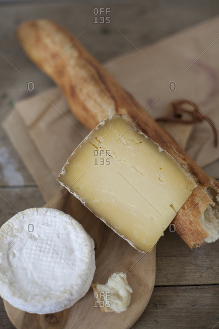 Top view of two types of cheese with a baguette