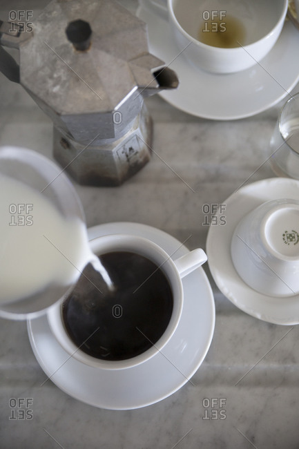 High angle view of pouring milk into coffee