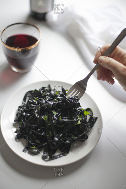 Eating squid ink pasta with chopped parsley