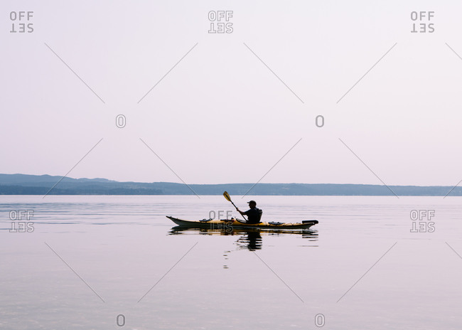 Man sea kayaking calm waters of Puget Sound, dusk