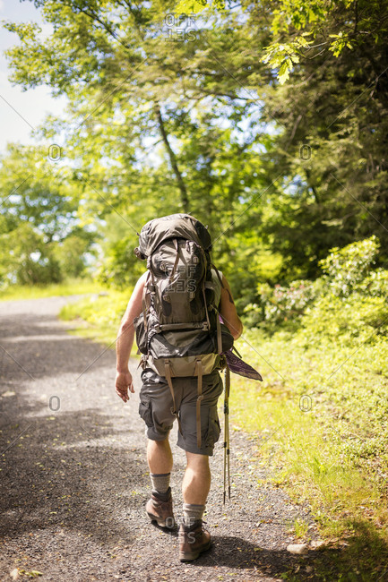 Man with back pack walking on path