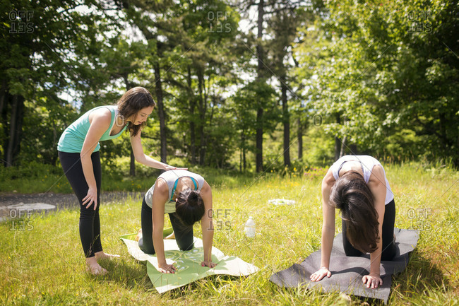 Yoga instructor helping student in nature