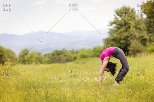 Woman on mountain doing yoga