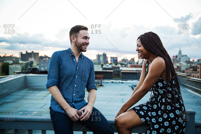 Man and woman talk and laugh at rooftop party, Brooklyn
