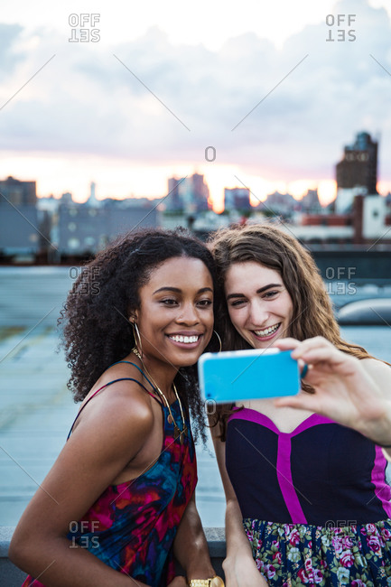 Friends taking a self-portrait at a rooftop party, Brooklyn