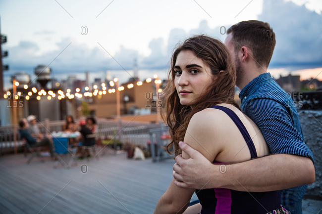 Couple at the edge of a rooftop party, Brooklyn