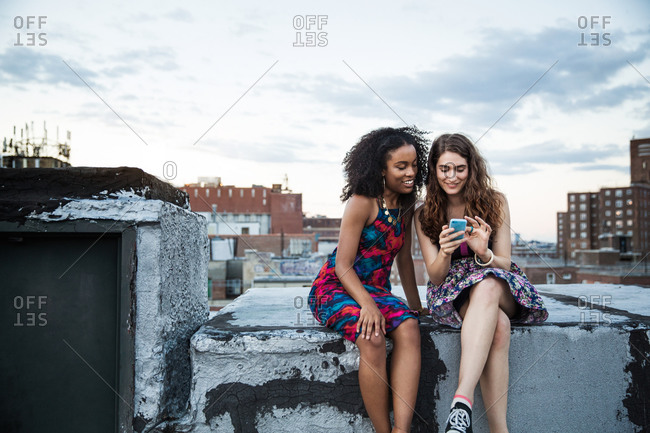 Two women looking at smartphone at rooftop party, Brooklyn