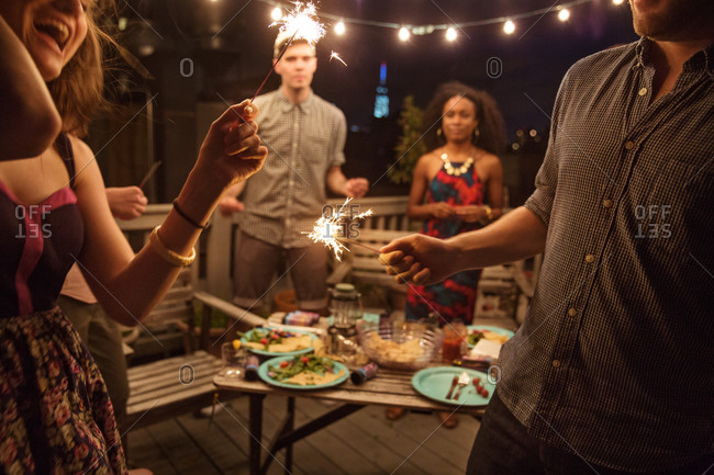 Young people with sparklers at rooftop party, Brooklyn