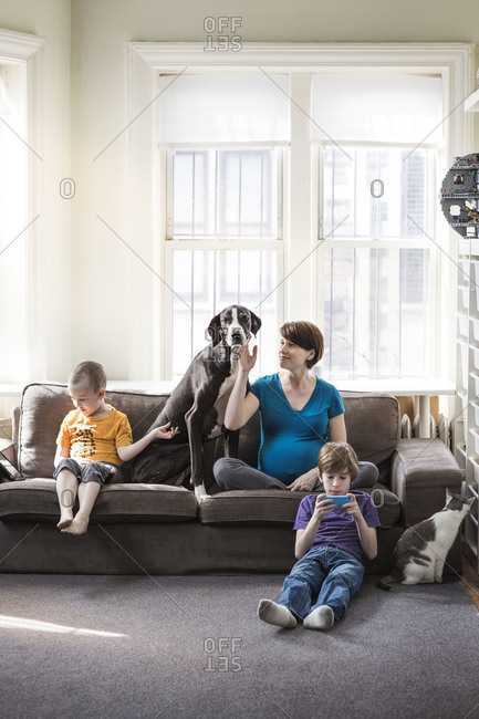 Pregnant mother, her two sons, and the cat and dog sit in the living room