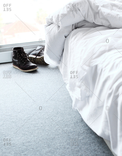 Shoes on a floor next to an unmade bed