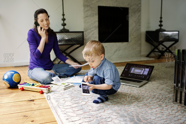 Mother working in living room while her son playing