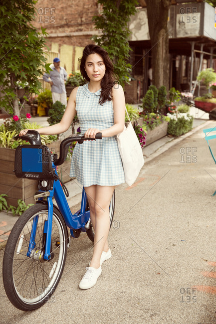 Young woman with rented bicycle