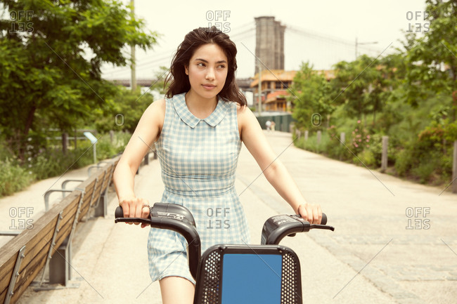 Young woman riding rented bicycle