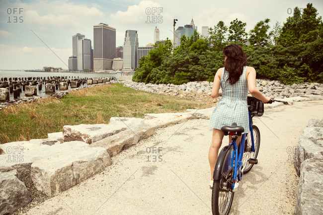 Woman with rented bicycle by the waterfront, Brooklyn