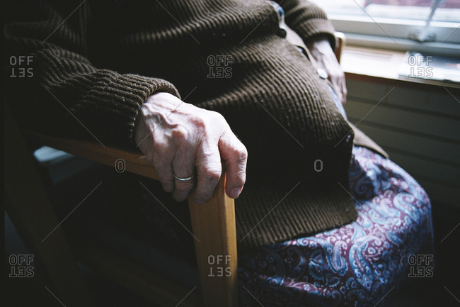 Mid-section of an elderly lady sitting in a hospital complex