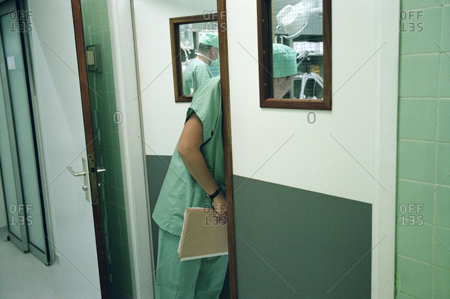 Surgeon peeping through the door of an operating room.