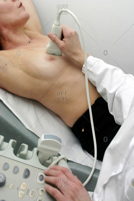 Woman undergoing a breast ultrasound examination in radiology room.
