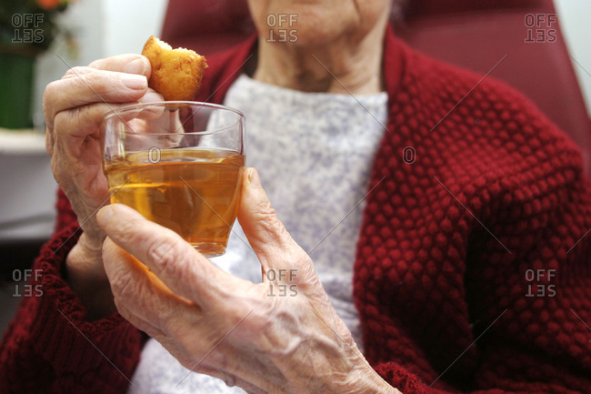 Mid-section of an elderly lady holding a hot beverage and biscuit in a nursing home