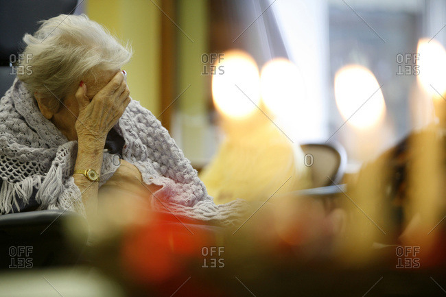 An elderly lady sitting with her hand on head in a nursing home