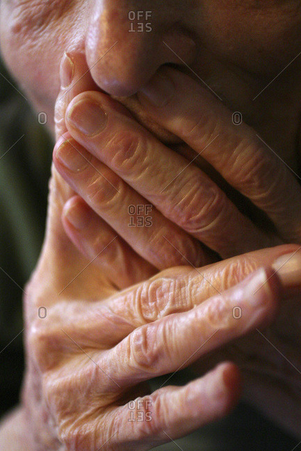 Close up of an elderly patient hands on face