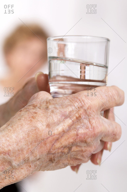 Close up view of an elderly patient holding a glass of water