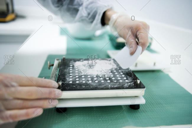 Laboratory technician preparing medical drugs using a measuring devise