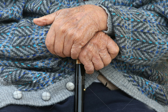 Mid-section of an elderly gentleman  holding a cane