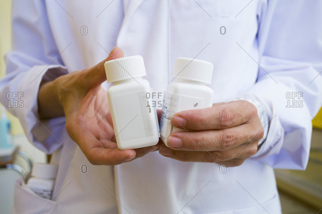 Close up view of a medical worker holding tubes of medicine