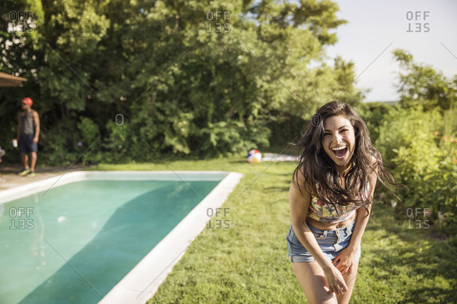 Woman laughing by a swimming pool
