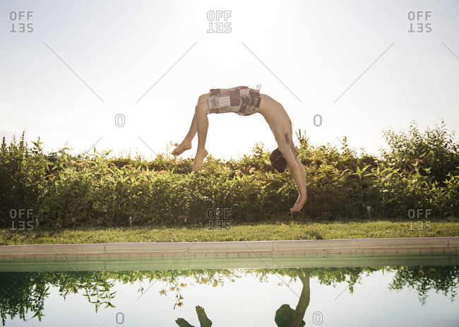 Man performs a backflip into the pool