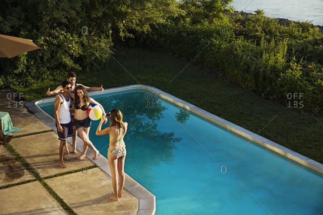 Group of friends taking a group picture by pool