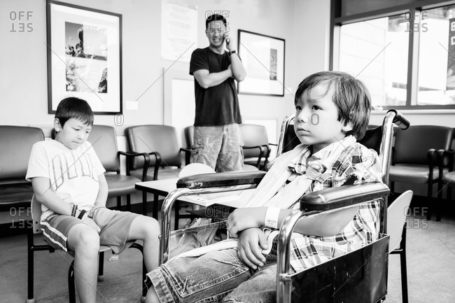 Boy with a broken arm sitting in a waiting room with his father and brother