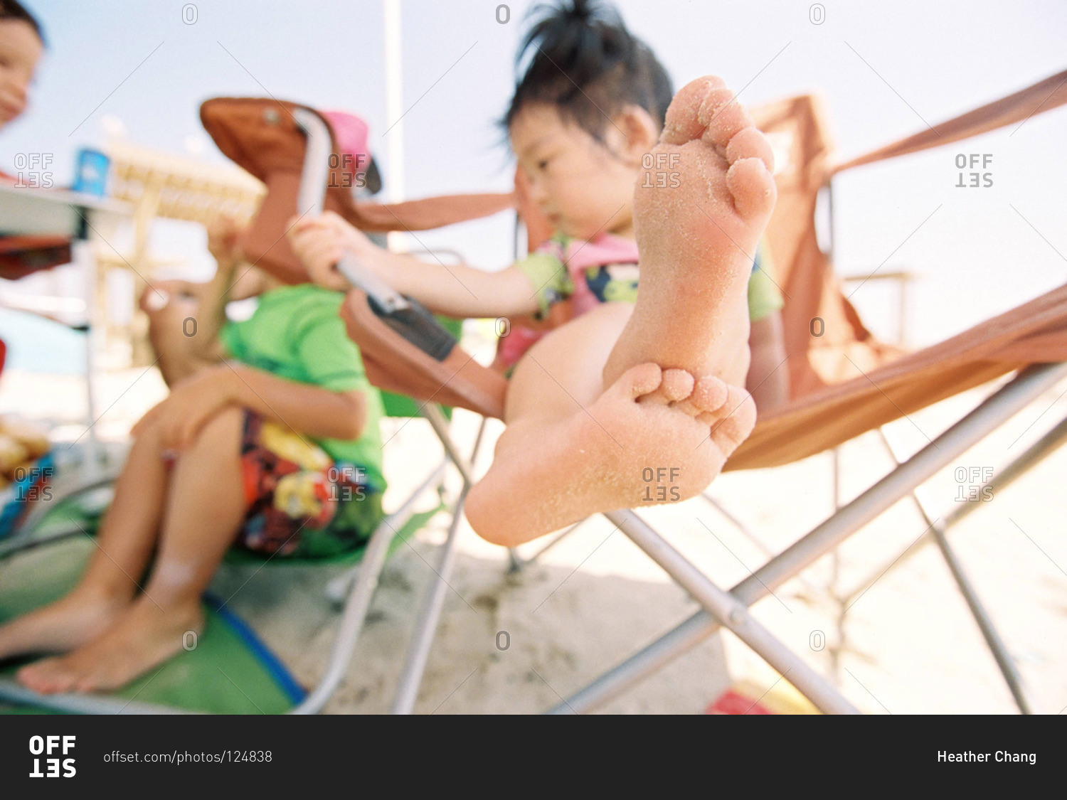 Little Girl Sitting In A Beach Chair With Sandy Feet Stock -4967