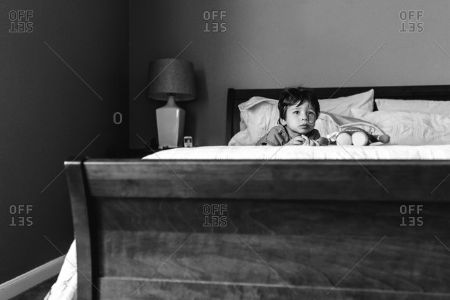 Young boy lying on a bed