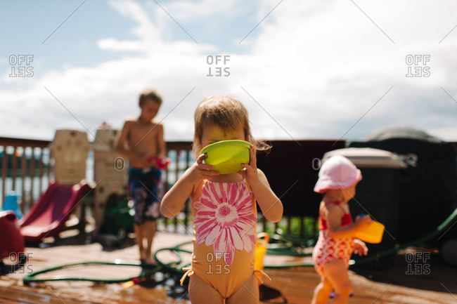 Girl drinking from a toy bucket
