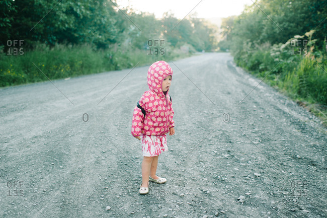 Girl standing on a dirt road wearing a hooded jacket
